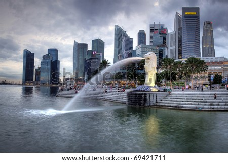 SINGAPORE-DEC 29: The Merlion fountain spouts water in front of the Singapore  skyline on Dec. 29, 2010.  Merlion is an imaginary creature with the head of a lion and the body of a fish and is often seen as a symbol of Singapore. - stock photo
