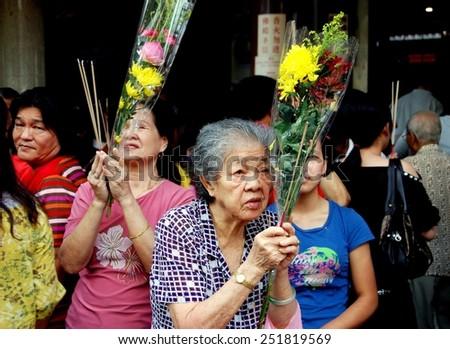 Singapore - December 13, 2007:  An elderly woman holding Chrysanthemums prays at the Kuan Im Thong Hood Cho Chinese Temple on Albert Mall - stock photo