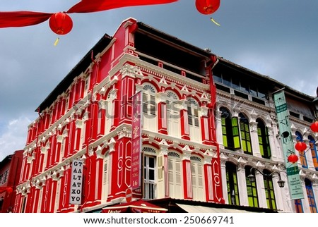 Singapore - December 14, 2007: Colourfully painted restored 19th century shop houses flanked by red Chinese lanterns on Temple Street in Chinatown - stock photo