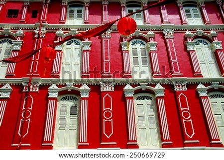 Singapore - December 14, 2007:  Finely restored late 19th century building painted in bright Chinese red with white wooden louvered shuttered windows on Temple Street in Chinatown - stock photo