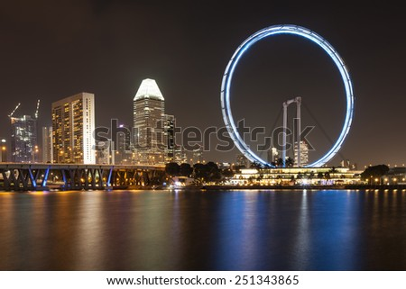 SINGAPORE - DECEMBER 10: Night view of the Singapore Flyer December 10, 2014 in Singapore. City skyline at night - stock photo