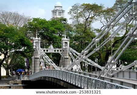 Singapore - December 11, 2007:  The 1868 Cavenagh Bridge spans the Singapore River leading to the Colonial Historic District - stock photo
