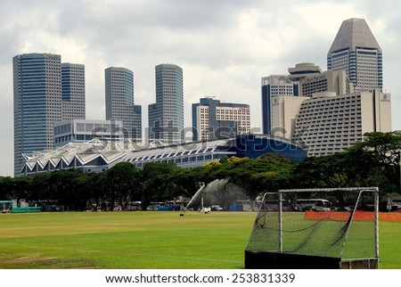 Singapore - December 12, 2007:  The historic Padang cricket field and Marina Square  modern towers skyline on the opposite shore of the Singapore River - stock photo