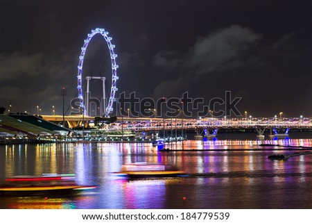 SINGAPORE - December 3, 2013: The view of Singapore's Marina bay featuring a Ferris wheel with boats passing below. - stock photo