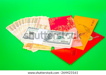 Singapore dollars note in a red envelope on a green background  - stock photo