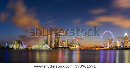 SINGAPORE - FEB 25, 2016: Cityscape panorama of Singapore city skyline with Marina Bay Sands hotel, ferris wheel and Gardens By The Bay at dusk in Marina Bay - stock photo