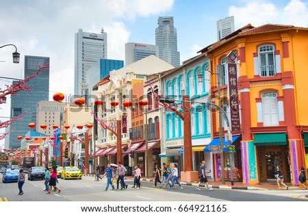 SINGAPORE - FEB 17, 2017: People crossing the road in Chinatown of Singapore. Modern skyscrapers of Singapore Downtown on a background.