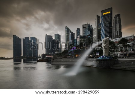 SINGAPORE FEB 11 : The Merlion fountain at night. Feb. 11, 2014 in Singapore. Merlion is an imaginary creature with a head of a lion and the body of a fish and is often seen as a symbol of Singapore. - stock photo