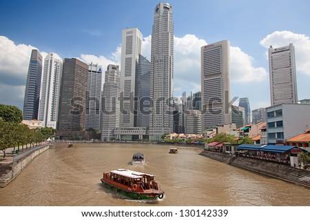 SINGAPORE - FEBRUARY 22: A tourist boat cruising Singapore river, on February 22, 2013 in Singapore. The Singapore River Cruise is a tourist attraction in this former British colony. - stock photo