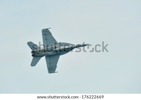 SINGAPORE - FEBRUARY 9: Aerobatic flying display by Royal Australian Air Force (RAAF) F-18 Hornet at Singapore Airshow February 9, 2014 in Singapore - stock photo