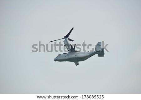SINGAPORE - FEBRUARY 9: Aerobatic flying display by US Air Force (USAF) MV-22 Osprey tilt-rotor aircraft at Singapore Airshow February 9, 2014 in Singapore - stock photo