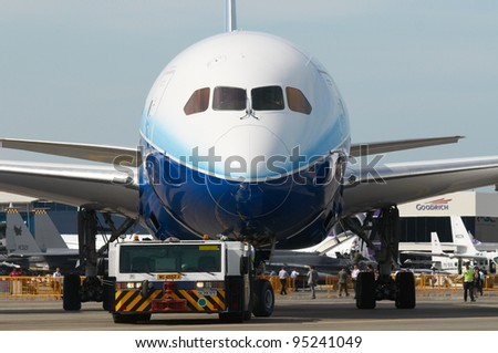 SINGAPORE - FEBRUARY 14: Boeing 787 Dreamliner being towed during Singapore Airshow at Changi Exhibition Centre in Singapore on February 14, 2012. - stock photo
