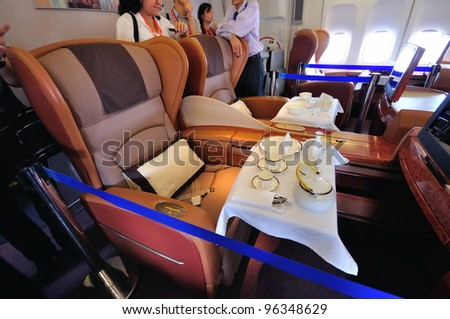 SINGAPORE - FEBRUARY 17: First class cabin with dining set on display in Singapore Airlines' (SIA) last Boeing 747-400 aircraft at Singapore Airshow on February 17, 2012 in Singapore - stock photo