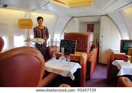 SINGAPORE - FEBRUARY 12: First class cabin with Singapore girl in Singapore Airlines' (SIA) last Boeing 747-400 aircraft at Singapore Airshow February 12, 2012 in Singapore - stock photo