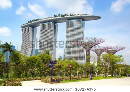 SINGAPORE - FEBRUARY 05, 2014: Marina bay sands and Supertree Grove at Gardens by the Bay.Gardens by the Bay is a park consists of three waterfront gardens: Bay South, Bay East and Bay Central Garden  - stock photo