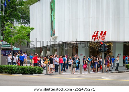SINGAPORE - 01 JAN 2014: People on pedestrians crossing on famous street Orchard Road in Singapore. Orchard Road is the most popular shopping enclave of Singapore and major tourist attraction. - stock photo