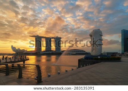 SINGAPORE-JAN 31: The Merlion fountain in front of the Marina Bay Sands hotel on January 31, 2015 in Singapore. Merlion is a imaginary creature with the head of a lion,seen as a symbol of Singapore - stock photo