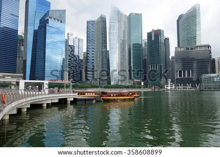 SINGAPORE - JAN 04, 2016: Tourist boat approaches the Raffles Landing Site in Singapore. The Singapore River Cruise is a tourist attraction in this former British colony.