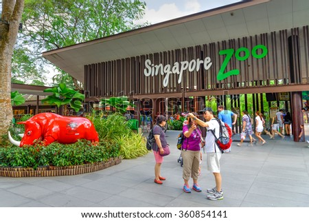 SINGAPORE-JAN 10, 2016: Visitors using smartphone, camera and selfie stick to take photo at the entrance of Singapore Zoo. With 315 species of animal, the zoo attracts 1.7 million visitors each year  - stock photo