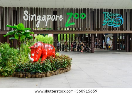 SINGAPORE-JAN 10, 2016: Visitors using smartphone, camera and selfie stick to take photo at the entrance of Singapore Zoo. With 315 species of animal, the zoo attracts 1.7 million visitors each year. - stock photo