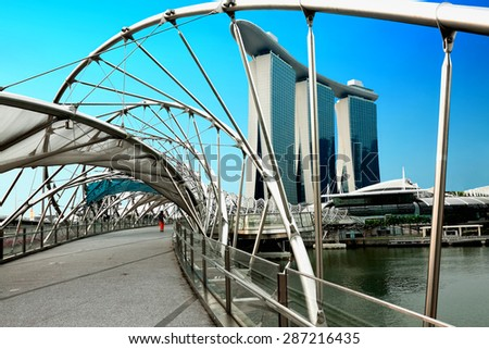 SINGAPORE - JANUARY 22, 2014: Helix Bridge and Marina Bay Sands in Singapore, Republic. Helix is fabricated from 650 tonnes of Duplex Stainless Steel and 1000 tonnes of carbon steel - stock photo