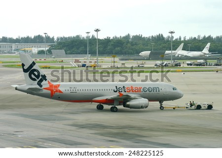 SINGAPORE - JANUARY 10:  Jetstar Asia Airbus 320 being pushed back at Changi Airport on January 10, 2015 in Singapore - stock photo