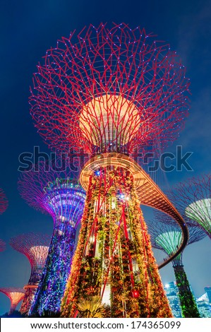 SINGAPORE -JANUARY 13: Night view of Supertree Grove at Gardens by the Bay on Jan 13, 2014 in Singapore. Spanning 101 hectares of reclaimed land in central Singapore, adjacent to the Marina Reservoir - stock photo