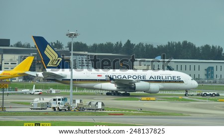SINGAPORE - JANUARY 10: Singapore Airlines Airbus 380 super jumbo being towed across taxi-way at Changi Airport on January 10, 2015 in Singapore - stock photo