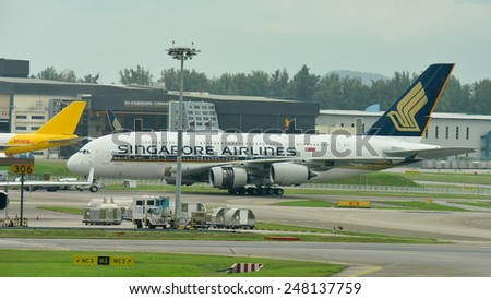 SINGAPORE - JANUARY 10:  Singapore Airlines Airbus 380 super jumbo towed out of hangar at Changi Airport on January 10, 2015 in Singapore - stock photo