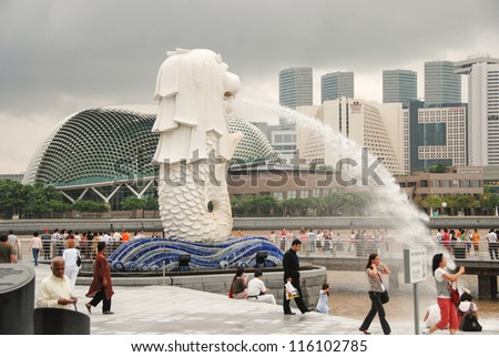 SINGAPORE - JUL 28: The Merlion fountain spouts water in front of the Singapore skyline on July 28, 2009. Merlion is an imaginary creature with the head of a lion, often seen as a symbol of Singapore - stock photo