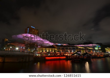 SINGAPORE- JULY 13 : A river cruise boat picks up tourists at Clarke Quay jetty on the Singapore River July 13, 2012 in Singapore. The Singapore river cruise ride is a popular tourist attraction. - stock photo