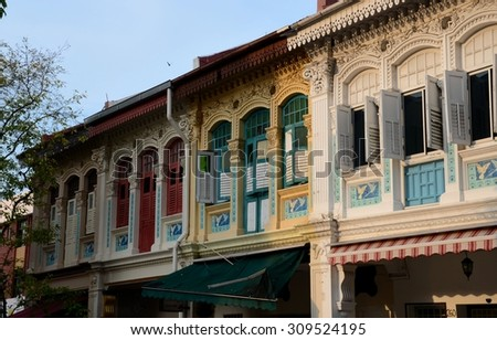 Singapore - July 13, 2015: A row of shop houses along Joo Chiat Rd. The Perenakan architecture mixes colonial Malay & Chinese designs. A shop house has a shop on ground floor & living quarters above. - stock photo