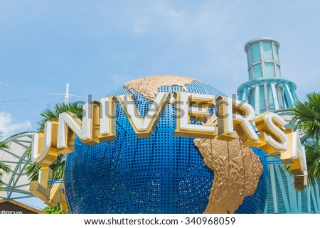 SINGAPORE - JULY 20: Tourists and theme park visitors taking pictures of the large rotating globe fountain in front of Universal Studios. - stock photo