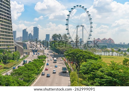 SINGAPORE - 01 JUN 2013: Cars traffic on Sheares ave with Singapore Flyer giant ferris wheel on background.  - stock photo