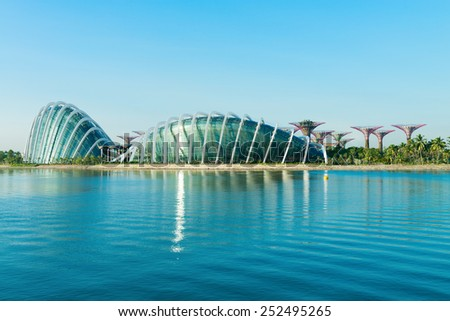 SINGAPORE - 01 JUNE 2013: Day view of the Supertree Grove, Cloud Forest & Flower Dome at Gardens by the Bay with reflection in Marina Bay water on front - stock photo