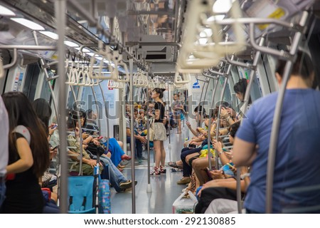 SINGAPORE-JUNE 26: Unidentified people on the Mass Rapid Transit train in Singapore on June 26, 2015. The Mass Rapid Transit has 102 stations and is the second-oldest metro system. - stock photo