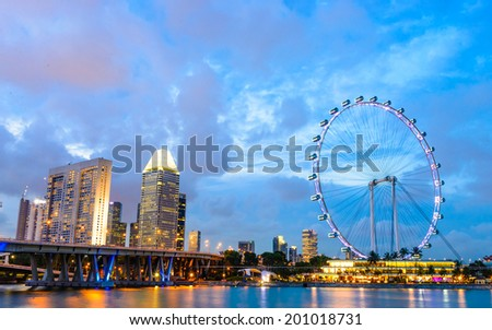 Singapore - June 26, 2014: View from distance to Singapore Flyer, huge ferries wheel and famous hotel and casino at Bayfront of Singapore. is round about 200 meters high and 340 meters wide. - stock photo