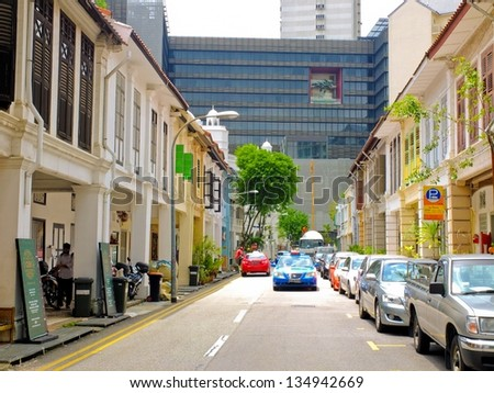 SINGAPORE - MARCH 9: Conserved shop houses in a modern city on March 9, 2013 in Singapore. Surrounded by modern buildings, Niven road's old shop houses have either been conserved or restored. - stock photo