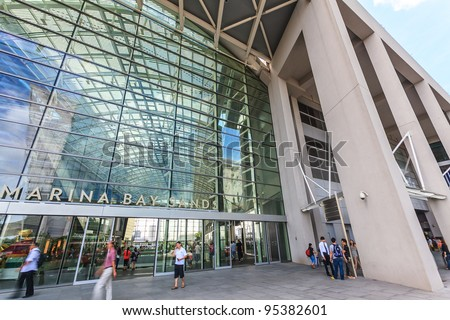 SINGAPORE-MARCH 13: Guests arrive Marina Bay Sands Resort Hotel on March 13, 2011 in Singapore. It is billed as the world's most expensive standalone casino property at S$8 billion. - stock photo