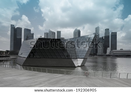 "SINGAPORE - MARCH 27, 2014 : Louis Vuitton at Marina Bay Sands. It is located in a floating ""Crystal Pavilion"" designed by Safdie Architects, an asymmetric building with irregularly angled facades. - stock photo"