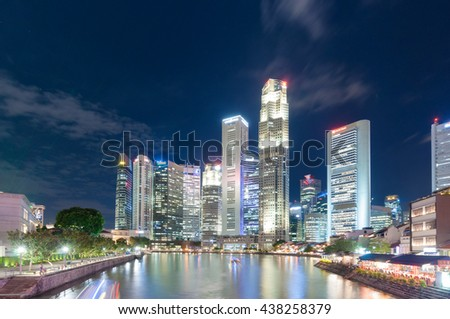 Singapore-March 12,2016 : Singapore city skyline with buildings in business district at night by Singapore river - stock photo