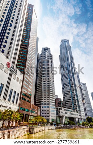 SINGAPORE - MARCH 18: Tall buildings of the financial district dot the Singapore River along Boat Quay Mar. 18, 2015. The area is the city's commercial center known as Central Business District (CBD). - stock photo