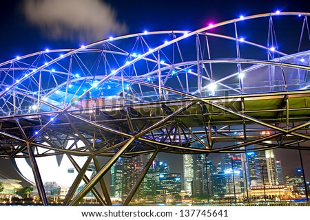 SINGAPORE - MARCH 06: The Helix Bridge at night on March 06, 2013 in Singapore.  The Helix is fabricated from 650 tonnes of Duplex Stainless Steel and 1000 tonnes of carbon steel. - stock photo