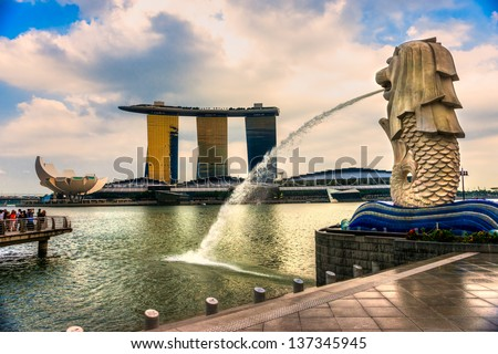 SINGAPORE-MARCH 19 : The Merlion and the Marina Bay Sands Resort Hotel, billed as the world's most expensive standalone casino property at S$8 billion on March 19, 2013 in Singapore. - stock photo
