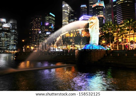 SINGAPORE - MARCH 07: The Merlion fountain spouts water in front of Singapore downtown on March 07, 2013 in Singapore. Merlion is an imaginary creature , often seen as a symbol of Singapore  - stock photo