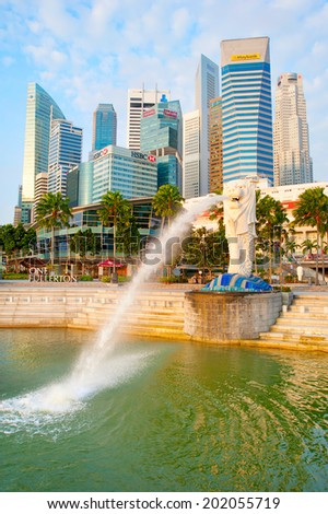 SINGAPORE - MARCH 08 2013 : The Merlion fountain spouts water in front of the Singapore downtown in Singapore. Merlion is a creature with a lion head, often seen as a symbol of Singapore  - stock photo