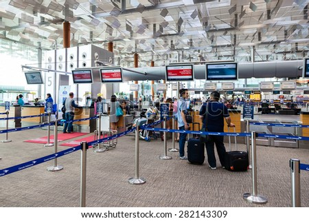 SINGAPORE - MARCH 24: Travelers preparing to check in at Changi Airport Terminal 3 departure hall Mar. 24, 2015. Opened in 1981, Changi Airport is a major transportation hub in Asia. - stock photo