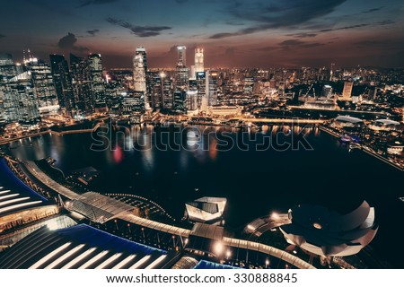 Singapore Marina Bay rooftop view with urban skyscrapers at night.   - stock photo