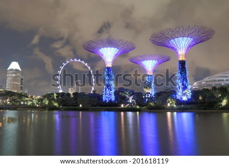 SINGAPORE - 28 May, 2014:Gardens by the bay Supertree Grove and Singapore Flyer. Gardens by the bay is a park spanning 101 hectares of reclaimed land in central Singapore.  - stock photo