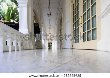 SINGAPORE - MAY 4 2009 : Interior of the Raffles Hotel  in Singapore. Opened in 1899, it was named after Singapore's founder Sir Stamford Raffles.  One of the most prestige hotel in Singapore. - stock photo